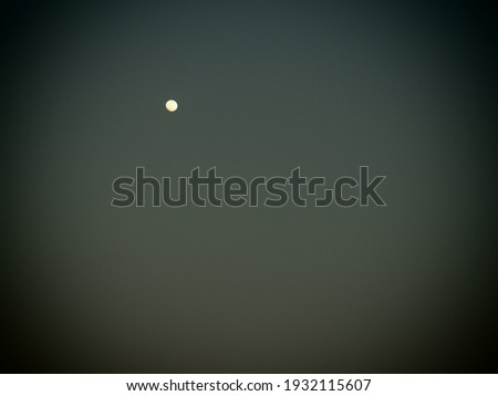 The moon in the night greenish sky. White point in the sky. Dark vignetting around the edges of the image