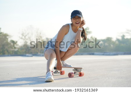 Asian women surf skate or skates board outdoors on beautiful summer day. Happy young women play surf skate at park on morning time.