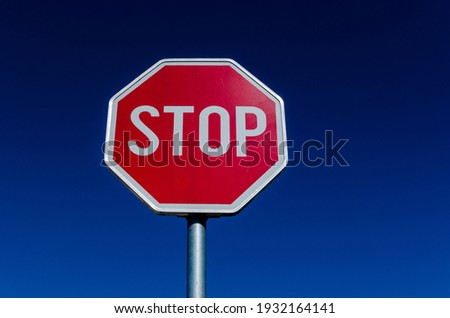 A traffic STOP sign and blue sky