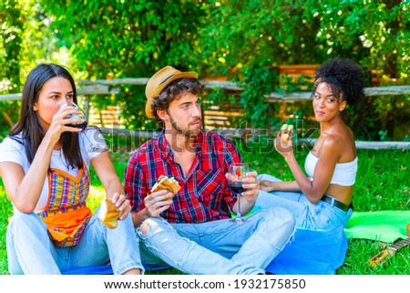 Group of friends having pic-nic in a park on a sunny day - People hanging out, having fun while grilling and relaxing The company of young people enjoys a summer green hlls picnic. People concept