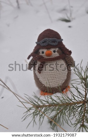 Knitted toy penguin stands in the forest in the snow.