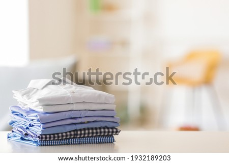 Stack of clean clothes on table in room Royalty-Free Stock Photo #1932189203