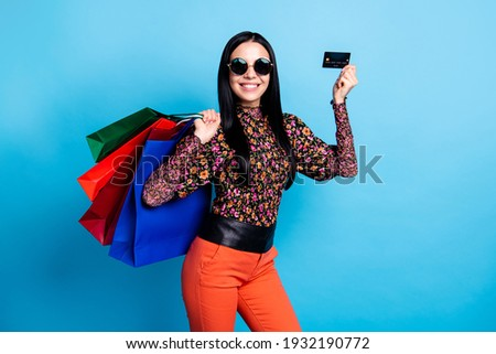 Photo of trendy brunette young woman hold plastic credit card bags sale isolated on blue color background