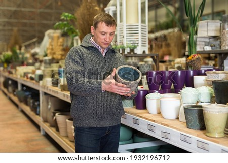 Male seller is standing near clay pots in stock. High quality photo