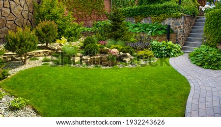 Garden stone path with grass growing up between the stones.Detail of a botanical garden. Royalty-Free Stock Photo #1932243626
