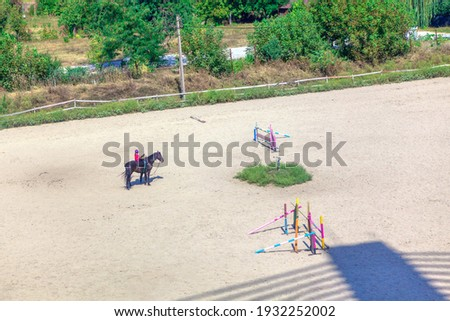jockey  riding horse during lesson in equestrian school . Equestrian terrain with obstacles and race terrain Royalty-Free Stock Photo #1932252002