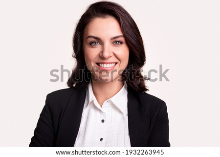Happy successful adult business lady in formal black jacket and white shirt looking at camera and smiling against white background Royalty-Free Stock Photo #1932263945