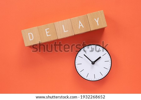 """Delay; Five wooden blocks with """"DELAY"""" text of concept and a simple clock. Royalty-Free Stock Photo #1932268652"""