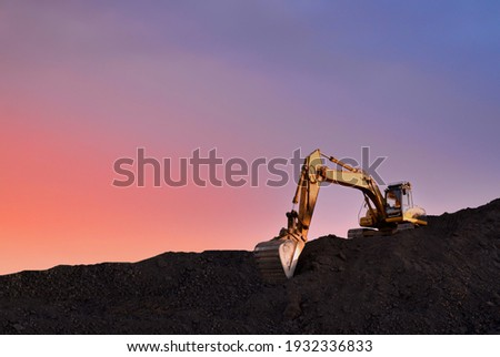Excavator working on earthmoving at open pit mining on sunset background. Backhoe digs sand and gravel in quarry. Heavy construction equipment during excavation at construction site Royalty-Free Stock Photo #1932336833