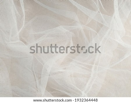 White mosquito net fabric texture with folds. Wavy chiffon background. Full frame of crumpled white cloth material texture. Abstract white net fabric pattern for patterns and designs. Royalty-Free Stock Photo #1932364448