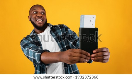 Cheap Tickets. Excited African Guy Holding Travel Tickets And Passport Standing On Yellow Studio Background. Joyful Tourist Guy Showing Boarding Pass. Book Your Trip Concet. Panorama