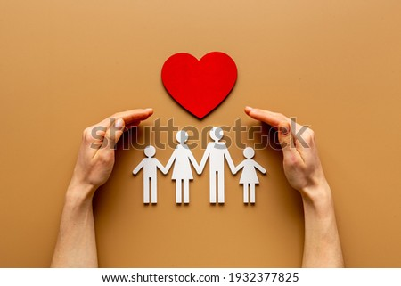Hands holding family figure. Life and health insurance concept. Royalty-Free Stock Photo #1932377825