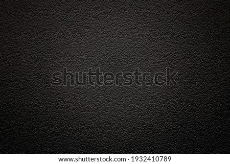 Dark background with fine texture and vignetting with emphasis on the center. An empty flat and clean surface for information. Advertising backdrop