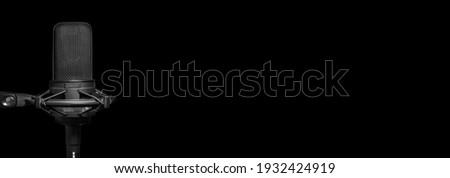 Professional recording studio microphone on black background with copy space. Media, music production or broadcasting banner Royalty-Free Stock Photo #1932424919