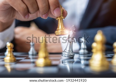 businessman hand moving gold Chess King figure and Checkmate opponent during chessboard competition. Strategy, Success, management, business planning, disruption and leadership concept Royalty-Free Stock Photo #1932441920
