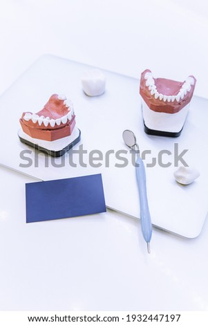 On the dentist's desk is a laptop, a business card, a dental mirror and a demonstrative model of teeth. Photo concept for the dental business. Space for the text.