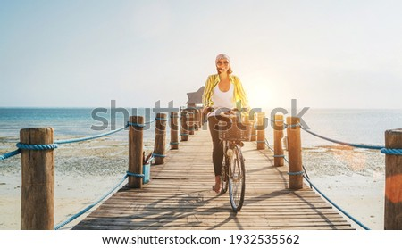 Portrait of a happy smiling woman dressed in light summer clothes and sunglasses riding a bicycle on the wooden sea pier and looking at camera. Careless vacation in tropical countries concept image Royalty-Free Stock Photo #1932535562