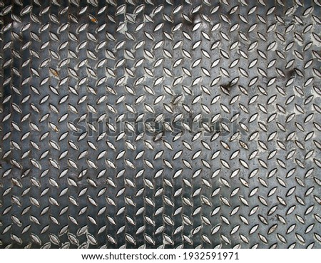 black diamond metal plate background, grunge texture of dark metallic sheet with small oval shape diagonal pattern, embossed surface prevents slipping for stair or walkway and ramp floor Royalty-Free Stock Photo #1932591971