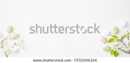 Flat lay easter frame with spring flowers and eggs on white background Royalty-Free Stock Photo #1932606266