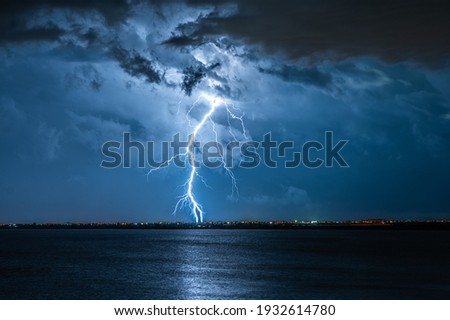 Strong electrical storm with a multitude of lightning strikes the ocean. Royalty-Free Stock Photo #1932614780