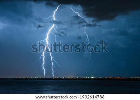 Strong electrical storm with a multitude of lightning strikes the ocean. Royalty-Free Stock Photo #1932614786