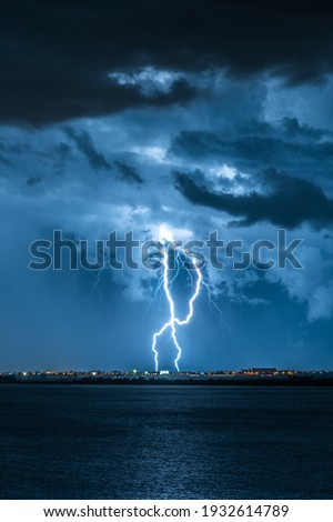 Strong electrical storm with a multitude of lightning strikes the ocean. Royalty-Free Stock Photo #1932614789
