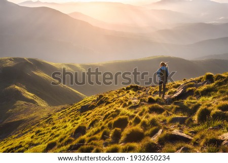 Girl on mountain peak with green grass looking at beautiful mountain valley in fog at sunset in summer. Landscape with young woman on the trail, foggy hills, forest, sky. Travel and tourism. Hiking Royalty-Free Stock Photo #1932650234