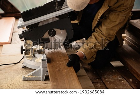 Miter saw with a large metal blade in the hands of a carpenter. Working tool for sawing wooden planks. A close-up of the sawing process. Labor protection and safety rules for the use of power tools. Royalty-Free Stock Photo #1932665084