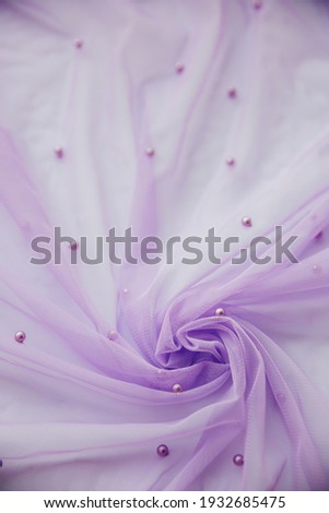Vertical macro picture of purple tulle fabric with small pearls swirling in wavy holds. Copy space for atelier card. Textured background for fashion card or blog, abstract pattern rippled into waves.