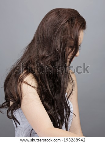 Portrait of a beautiful brunette woman with face hidden by long messy hair against gray background #193268942