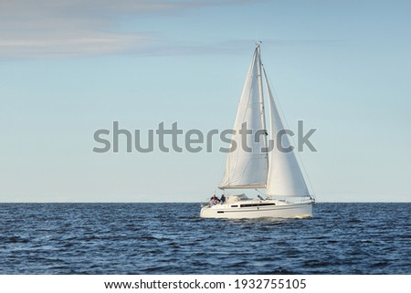 White sloop rigged yacht sailing in the Baltic sea at sunset. Clear sky after the storm, soft sunlight. Transportation, travel, cruise, sport, recreation, leisure activity, racing, regatta Royalty-Free Stock Photo #1932755105