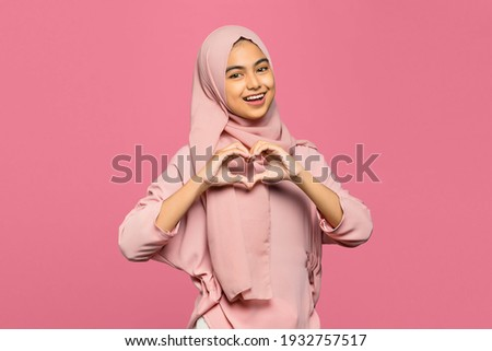 Portrait of attractive young Asian woman makes heart shape gesture with smiling face Royalty-Free Stock Photo #1932757517