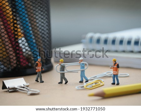 There is miniature toys and paper clip on the table with blurred book and stationery stuff as a backgorund. Office and worker business concept. Royalty-Free Stock Photo #1932771050