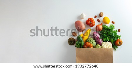Delivery healthy food background. Healthy vegan vegetarian food in paper bag vegetables and fruits on white, copy space, banner. Shopping food supermarket and clean vegan eating concept Royalty-Free Stock Photo #1932772640
