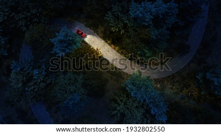 Adventure night road trip in the forest, aerial view of a car headlights on deep jungle road. Mystery concept. Royalty-Free Stock Photo #1932802550