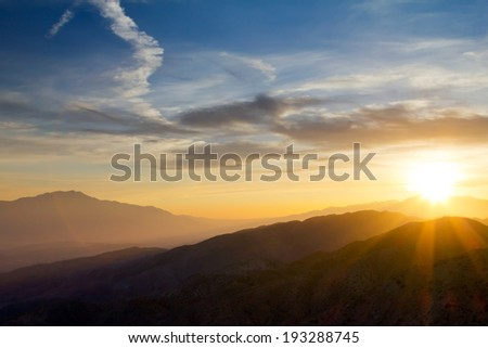 Colorful sunset rays over distant mountains in Joshua Tree National Park, California