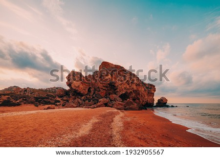 Sunset at sea. Scenic view of the sea, rocky coastline and sandy beach, golden sky and sun, outdoor travel background. General's beaches. Crimea. Royalty-Free Stock Photo #1932905567