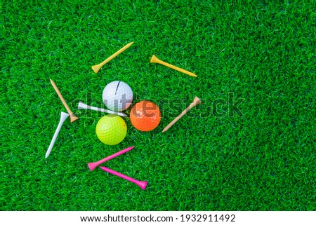 Golf glove ,colorful ball ,tee and gold club put on green grass of golf course ,This objects for play Royalty-Free Stock Photo #1932911492