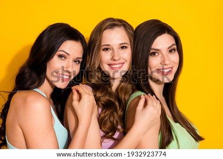 Photo of young happy smiling lovely sisters best friends hug embrace each other isolated on yellow color background
