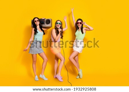 Full size photo of young happy excited crazy girls in sunglass listen boombox sing karaoke isolated on yellow color background