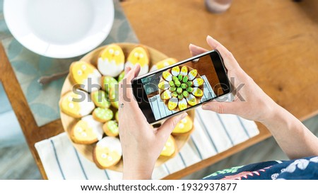 A food blogger takes pictures of an egg-shaped Easter sugar cookie on a smartphone. The influencer takes pictures of iced cookies with cute chickens. Easter baking ideas for kids.