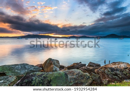 Drizzly day waterscape sunrise with boats from Koolewong Waterfront on the Central Coast, NSW, Australia. Royalty-Free Stock Photo #1932954284