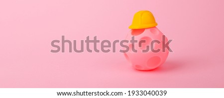 ball with craters in helmet over pink background, concept of housing construction for displaced people, panoramic mock-up