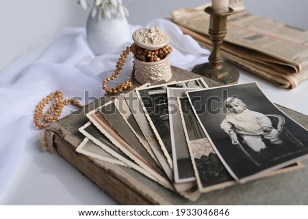 stack of vintage photos, baby photography of 50s, 60s, candle is lit, first spring flowers, snowdrop, Galanthus in vase, concept of family tree, genealogy, childhood memories