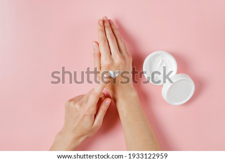Revitalizing hand cream for healing and recovery after excessive use of soap and disinfectants. Young woman applying moisturizing lotion. Copy space, close up, pink background, flat lay, top view.