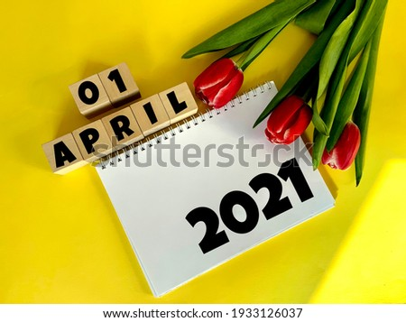 April 1 on wooden cubes.Next to it are tulips and a white notebook with the inscription 2021 on a yellow background.Calendar for April. Royalty-Free Stock Photo #1933126037
