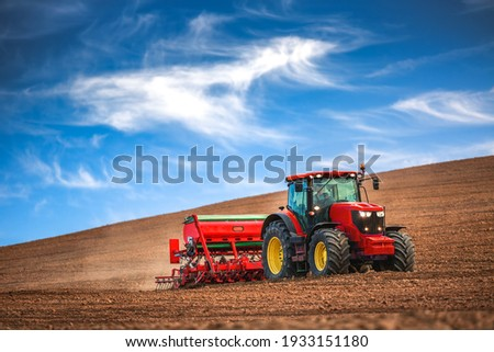 Farmer in tractor preparing farmland with seedbed for the next year Royalty-Free Stock Photo #1933151180