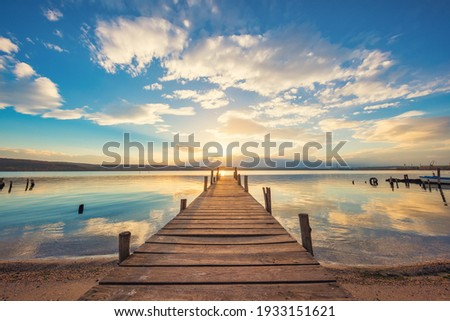 Old wooden dock at the lake, sunset shot Royalty-Free Stock Photo #1933151621