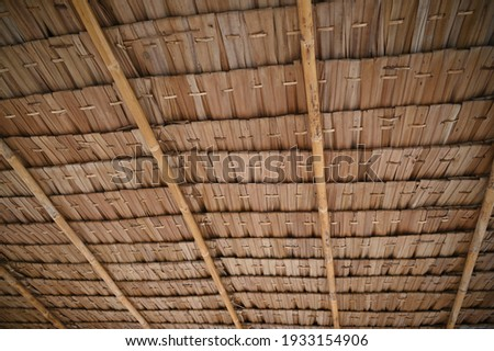 View from the southern side of a traditional thatched roof in a rural village. That thatched roof can be sunproof and rainproof. And good ventilation Background of hay or old hay Royalty-Free Stock Photo #1933154906