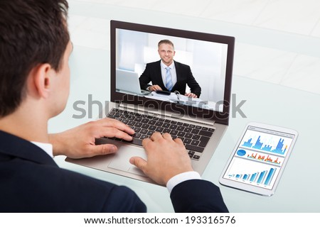 Cropped image of young businessman video conferencing on laptop at desk in office #193316576